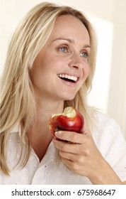 Woman with long blonde hair, wearing a white blouse, smiling and holding a fresh red apple