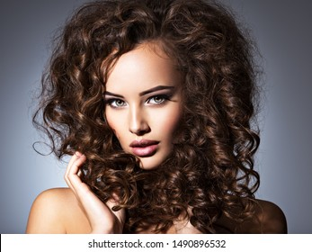 woman with long bown curly hair. Portrait of a Beautiful Brunette sexy girl with long hair