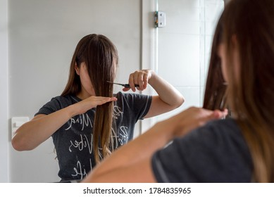 Woman with long brown hair cutting her own bangs