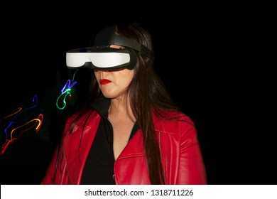 Woman with long brown hair with red jacket living augmented reality experience with special glasses to observe augmented reality in this case abstract image of light that simulates a cat