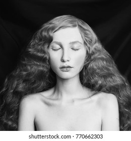 Woman with long curly flowing hair on a black background. Black and white art monochrome photography.