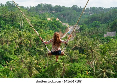 Woman with long curly hair swinging in the jungle, Bali. Rain forest and village on the background