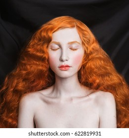 Woman with long curly red flowing hair on a black background. Red-haired girl with pale skin, blue eyes, bright unusual appearance without makeup. Natural beauty. The girl from the era of renaissance