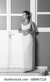 Woman in long dress posing on white door Studio shoot