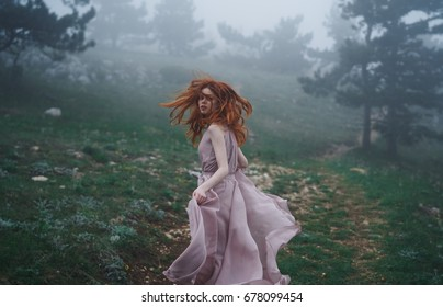 Woman in a long dress runs in the forest, fog