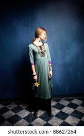 woman in long dress stand in empty room hold orchid in one hand