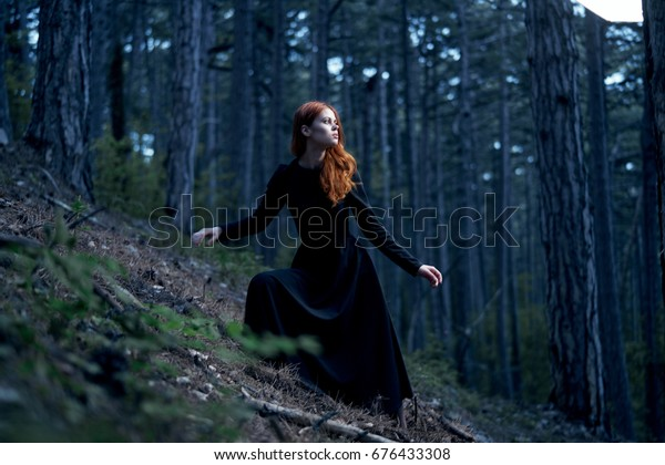 A woman in a long dress is walking through the forest in the dark, loneliness