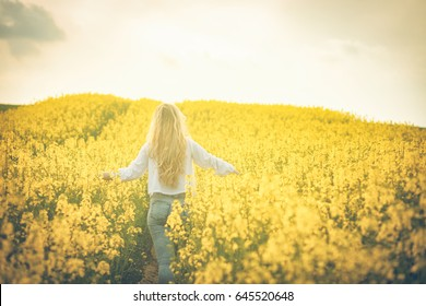 Woman with long hair back view, yellow rapeseed field at sunset