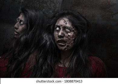 woman with long hair disguised as a zombie, reflecting in a mirror, with dark background