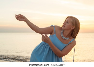 Woman with long hair in a dress dancing near the sea