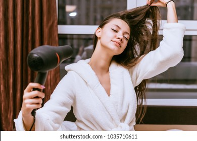 woman with long hair dries hair with a hairdryer