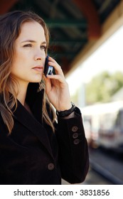 Woman with long hair and jacket talking on cell phone