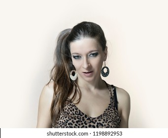 A woman with a long hair, leopard earrings dressed in decolletage shirt looking straight in to the camera
