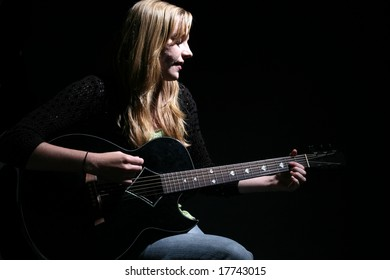 woman with long hair playing guitar and singing