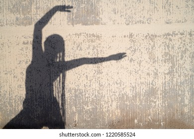 Woman with long hair posing against decayed sunlit wall.