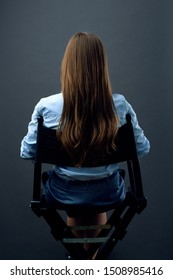 woman with long hair  sitting back on movies director chair. isolated female portrait.