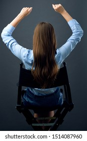 woman with long hair  sitting back on movies director chair with hands up. isolated female portrait.