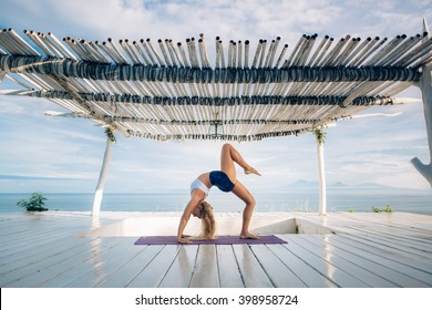 Woman with long hair and slim body make morning yoga exercise on the yoga mat on white wooden terrace. Yoga pose. Bridge pose.