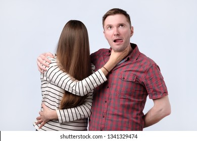 Woman with long hair try to strangle husband, studio shot. Family problems concept.