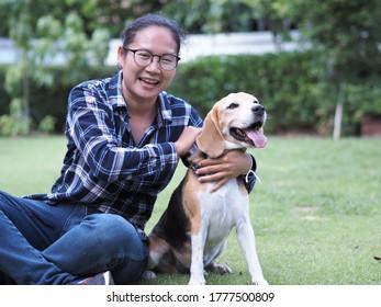 長い髪をし、スコティッシュの青と白の柄のシャツを着、眼鏡をかけ、青いジャンのパンツをはき、庭で犬と遊ぶ。