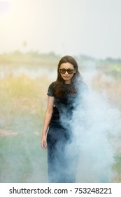 Woman with long hair wearing glasses Long black shirt and skirt Playing with color smoke on a natural background.