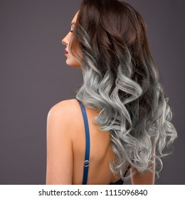 Woman with Long Healthy Colorful Ombre Grey Wavy Hair. Close Up of Hairstyle. Care and Hair Products