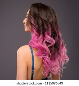 Woman with Long Healthy Colorful Ombre Pink Wavy Hair. Close Up of Hairstyle. Care and Hair Products
