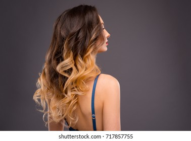Woman with Long Healthy Colorful Ombre Wavy Hair. Close Up of Hairstyle. Care and Hair Products