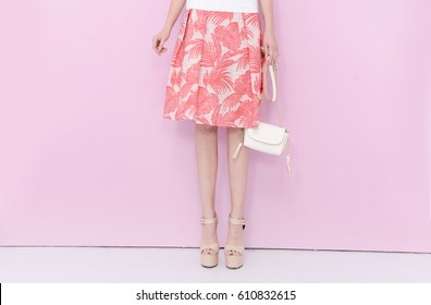 Woman long legs in fashion dress, high heels. Perfect female sexy legs, stylish skirt and summer glamour shoes ,bag on pink background