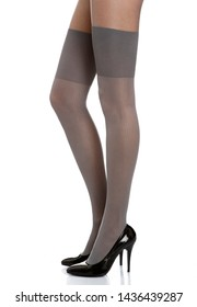 Woman with long legs wearing grey stylish panty hose stockings and black high heels stands from the left side on white isolated background
