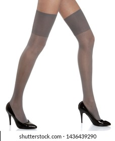 Woman with long legs wearing grey stylish panty hose stockings and black high heels steps to the right side on white isolated background