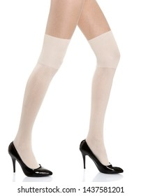 Woman with long legs wearing white stylish panty hose stockings and black high heels steps to the right side on white isolated background_1