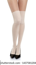 Woman with long legs wearing white stylish panty hose stockings and black high heels stands from the front side on white isolated background