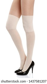 Woman with long legs wearing white stylish panty hose stockings and black high heels stands from the left side on white isolated background