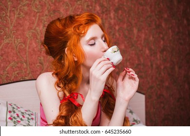 Woman with long red curly hair in a braid and a doll hands, in nightgown in bed under a blanket. Red-haired girl with pretty face, pale skin, blue eyes and bright unusual appearance bedroom