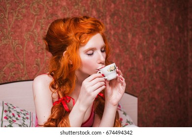 Woman with long red curly hair a braid and a doll in hands, in nightgown in bed under a blanket. Red-haired girl with pretty face, pale skin, blue eyes and bright unusual appearance the bedroom