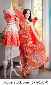 Woman in Long Red Floral Dress in Fashion Store - Portrait of girl in a clothes shop in a maxi summer dress