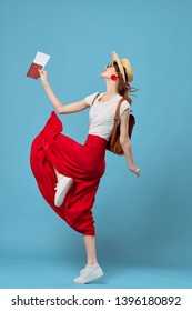 A woman in a long skirt and a headdress lifted her leg up and holds in her hand tickets for the plane