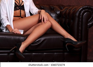 Woman with long slim legs sitting on a brown leather sofa