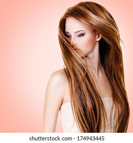 Woman with  long straight hairs over pink background