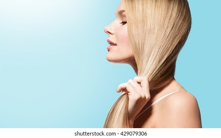 Woman with long thick straight hair in sun on a blue background in profile
