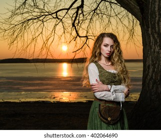 Woman with long wavy hair in the historical dress on the sunset