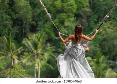 Woman in long white dress swinging in the jungle, Bali.