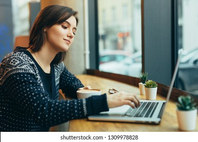 Woman Look Around And Smile While Work In Cafe On Her Laptop. Portrait Of Stylish Smiling Woman In Winter Clothes Work At Laptop. Female Bussiness Style With Sun. - Image