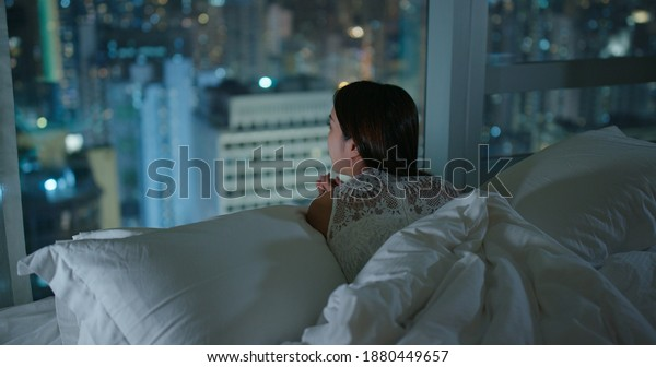 Woman look at the city view and lying on bed at night