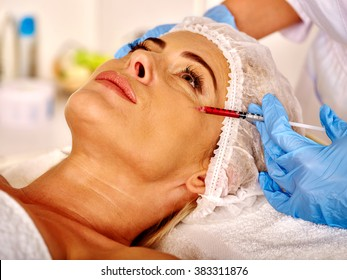 Woman look up middle-aged in spa salon with beautician. Beauty female giving botox injections.