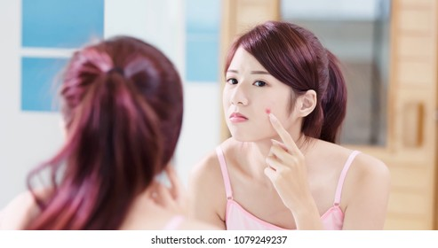 woman look mirror with acne problem in the bath room