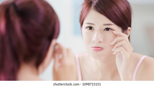 woman look mirror and touch her eyes in the bath room