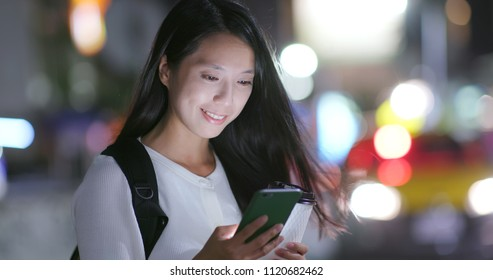 Woman look at the mobile phone in city at night