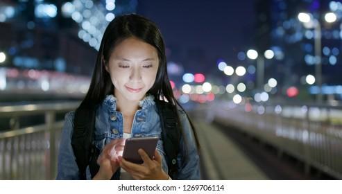 Woman look at mobile phone at night